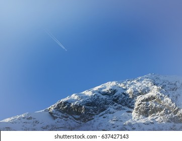 Airplane trail in blue sky with snowy mountain