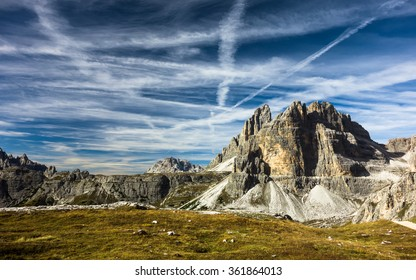 airplane trails on blue sky over peaks in italian dolomites scenery