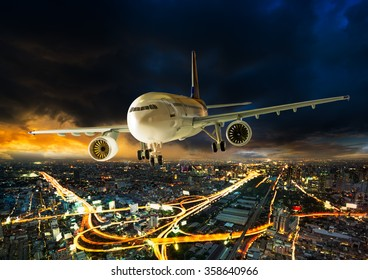 Airplane for transportation flying over the night scene city on beautiful sunset background