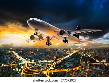 Airplane for transportation flying over the night cityscape on storm cloud in sunset time
