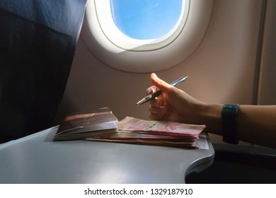 Airplane tray table on seat back inside cabin; one hundred thousand rupiahs, Indonesian currency and customs declaration form with sun shining through the window. Travel lifestyle vacations concept.