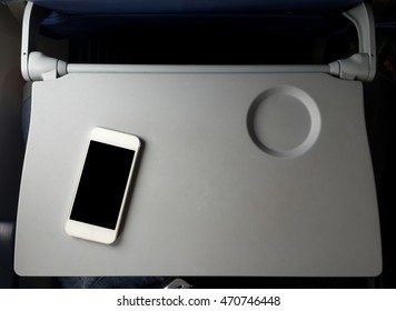 Airplane tray table on seat back with smartphone