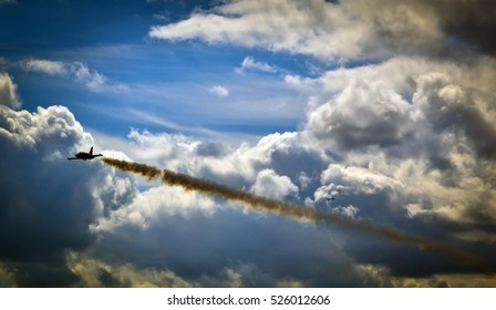 An airplane with vapor trails flying in blue cloudy sky