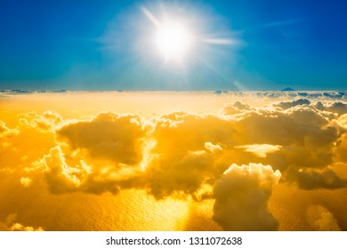 Airplane view of beautiful landscape with gold colored clouds, ocean with mountain peak and bright sunset shining sun