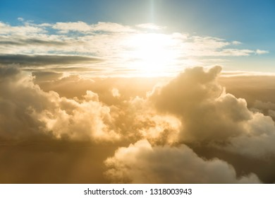Airplane view of beautiful landscape with gold colored clouds, ocean and bright shining sun