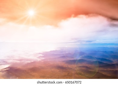 Airplane view with sky, clounds and mountains against the shining sun