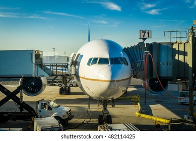 Airplane waiting on the tarmac receiving maintenance in early morning sunlight