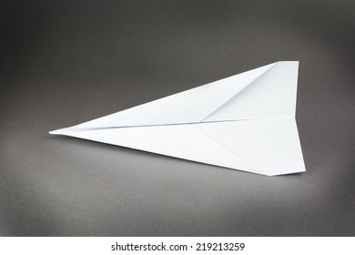 airplane of white paper on a gray background