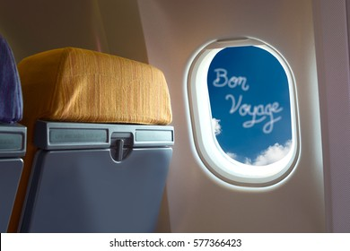 Airplane window with bon voyage could and blue sky