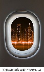 Airplane window from interior of aircraft with modern  megalopolis city view at night.