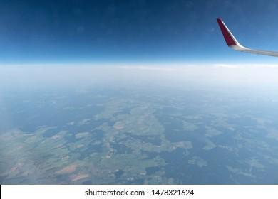 Airplane window view to cloudy sky and earth. Beautiful landscape from aircraft cabin. Flying without fear of flying, incidents and turbulence.