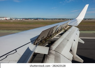 An airplane window view of wing and flaps after landing.