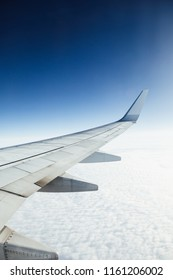 airplane wing against clouds and blue sky background