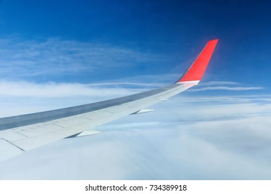 Airplane wing in blue sky viewed through the illuminator