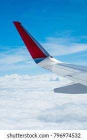 An airplane wing and clear blue sky