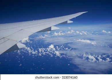 Airplane wing flying above the clouds with blue sky.