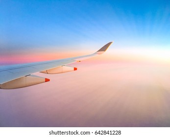 Airplane wing on beautiful clouds with the blue and pink sky background, view from window plane, twilight sky