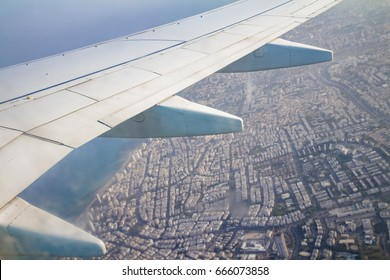 Airplane wing on the sky and over land with building of Tel Aviv city and the Mediterranean sea.