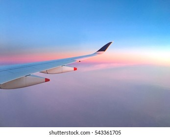 Airplane wing on twilight sky and clouds background