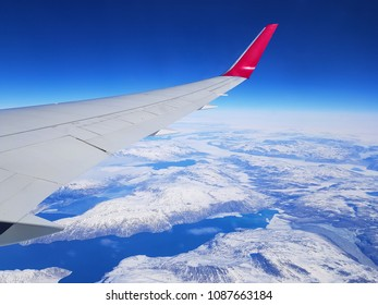 Airplane wing out of window. Flying above the mountains Snow tops. Blue sky, ocean. View from plane. Travel background.