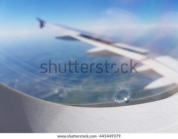 Airplane wing seen through window with pressure releas hole between glass