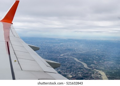 Airplane wing, Sky and Bangkok city as seen through window of an aircraft