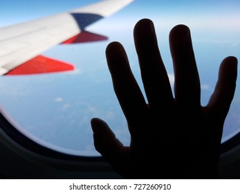 airplane wing and sky with hand on window