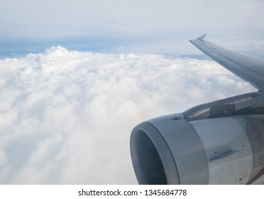 Airplane wing with turbofan engine and winglet over sea of clouds.