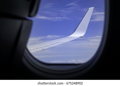 An airplane wing view from window with blue sky and clouds