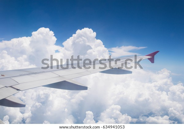 airplane wings with cloud and blue sky view from plane windows