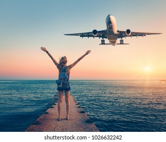 Airplane and woman at sunset. Summer landscape with girl standing on the sea pier with raised up arms and flying passenger airplane. Woman and landing commercial plane in the dusk.Lifestyle and travel