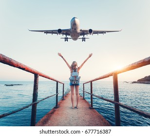 Airplane and woman at sunset. Summer landscape with girl standing on the sea pier with raised up arms and flying passenger airplane. Woman and landing commercial plane in the evening. Lifestyle