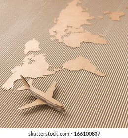 Airplane and world map made of cardboard. Shipping concept.