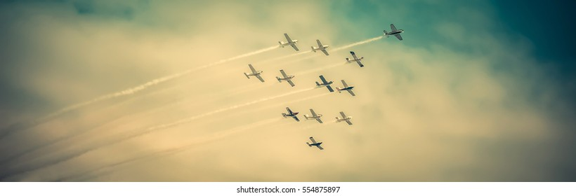 Airplanes flying high, in formation, during airshow, on dramatic sky, vintage effect applied.