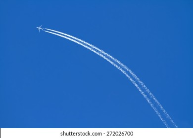 Airplanes leaving arch trace on a clear blue sky.