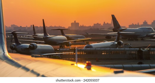 Airplanes on the runway ready to takeoff. Airport sunset.