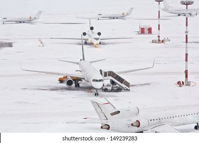 Airplanes and serving machinery on snowy airfield.