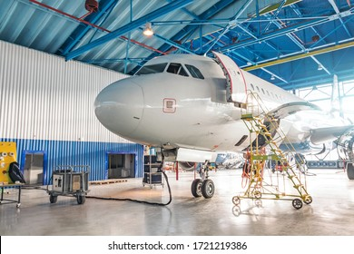Airplanes under repair in a maintenance hangar. View of the nose and cockpit, open front door with a technical staircase