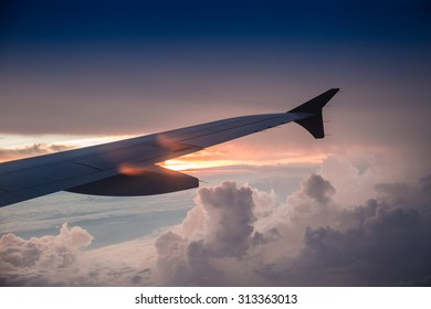 Airplane's wing against golden sunlight in early morning