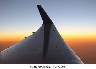 An airplane's wing in the air during sunset