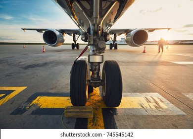 Airport at the amazing sunset. Low angle view of the airplane at the airport against. Member of the ground staff preparing the passenger airplane before flight. - Selective focus on the wheels.