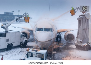 Airport attendant washing airplane in winter weather at an airport