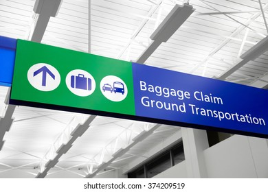Airport baggage claim and ground transportation sign with suitcase, bus, and taxi symbols. Sign is blue and green and hangs from the ceiling.