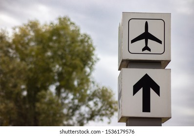 At the airport in Berlin. Two white signs show the way to the airport entrance. A sign shows a thick black arrow and the other sign a pictogram with a plane symbol.