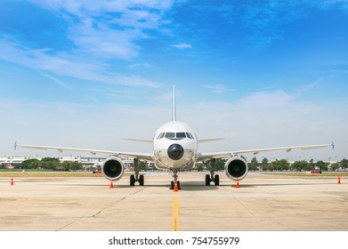 Airport building and airplane on runway.