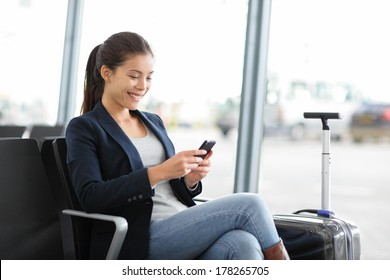 Airport business woman on smart phone at gate waiting in terminal. Air travel concept with young casual businesswoman sitting with hand luggage suitcase. Beautiful young mixed race female professional
