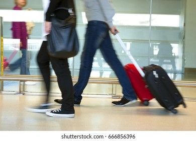 Airport commuters with luggage rushing in corridors