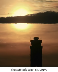 Airport Control Tower in silhouette against dramatic sunset sky