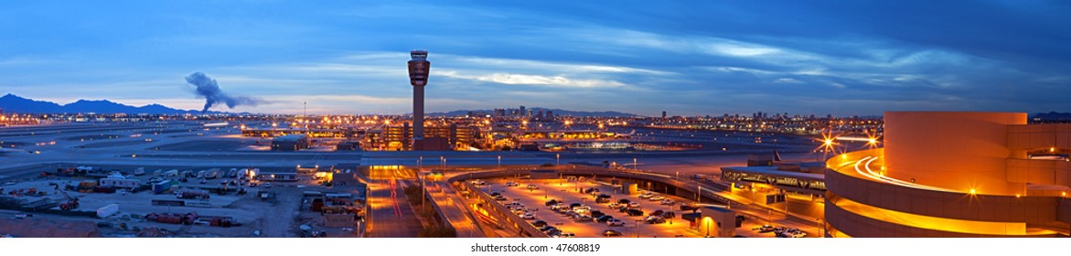 Airport at dusk, with city lights in back.