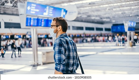Airport european nerd man in glasses and plaid shirt with luggage tourist boarding plane taking a flight  wearing face mask. Coronavirus flu virus travel